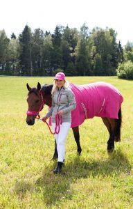 ピンクのラグを着た馬を曳く若い女の子